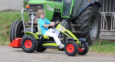 ילד רוכב על טרקטור פדלים עם כף הרמה